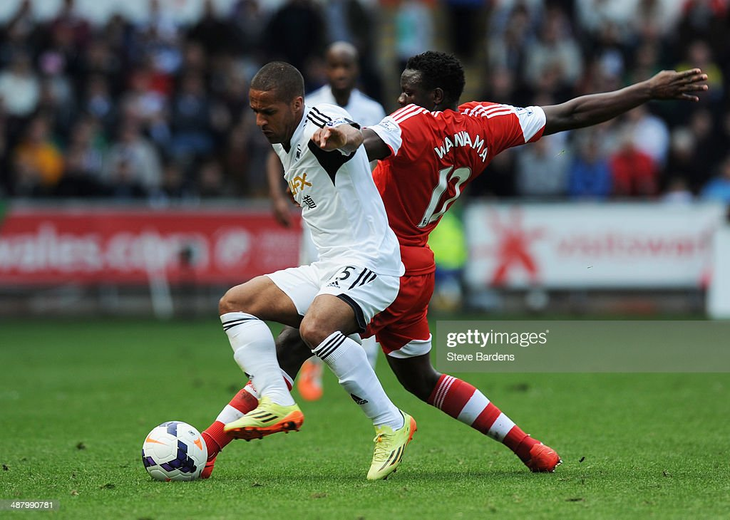 Wayne Routledge of Swansea City takes on Victor Wanyama of Southampton (12) during the Barclays Premier League match between Swansea City and Southampton at Liberty Stadium on May 3, 2014 in Swansea, Wales.