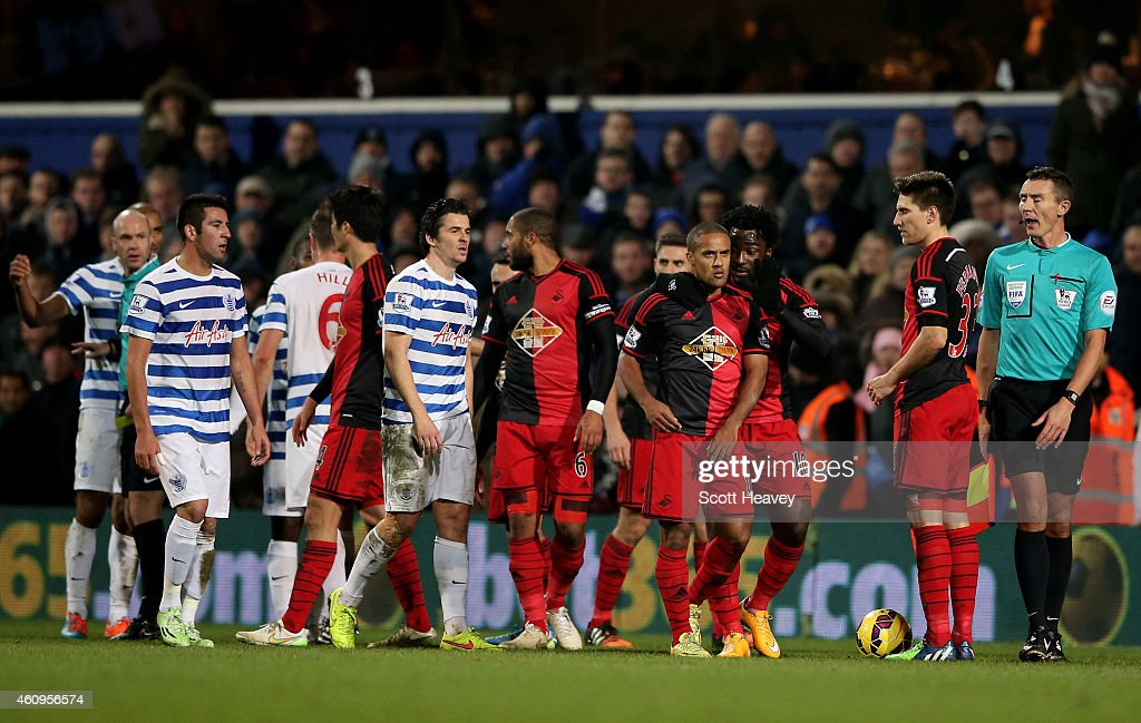 Wayne Routledge of Swansea City walks away prior to eceiveing the red card from referee Anthony Taylor for a foul on Karl Henry of QPR during the Barclays Premier League match between Queens Park Rangers and Swansea City at Loftus Road on January 1, 2015 in London, England.