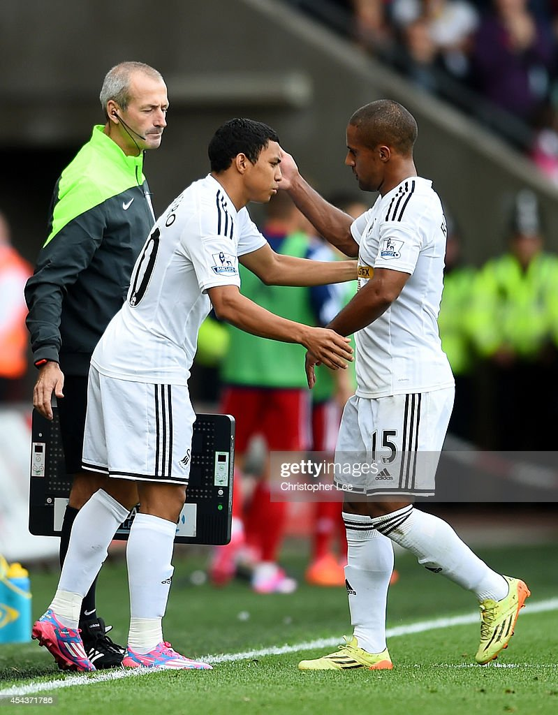 Wayne Routledge (R) of Swansea is substituted for Jefferson Montero during the Barclays Premier League match between Swansea City and West Bromwich Albion at Liberty Stadium on August 30, 2014 in Swansea, Wales.