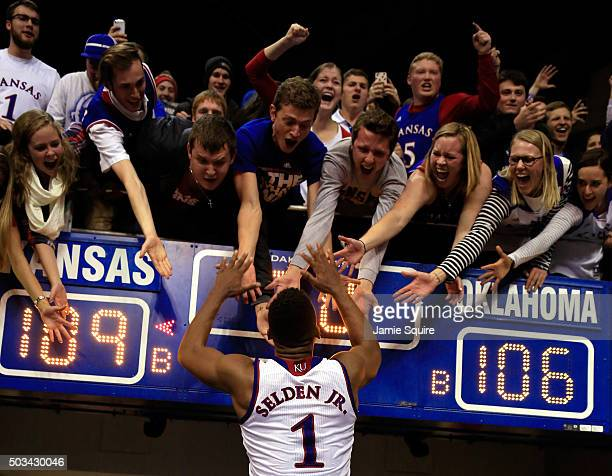 Wayne Selden Jr #1 of the Kansas Jayhawks celebrates with fans as he leaves the court after the Jayhawks defeated the Oklahoma Sooners 109106 in...