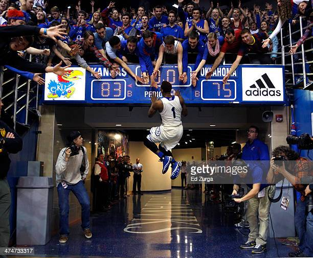 Wayne Selden, Jr. #1 of the Kansas Jayhawks slaps the scoreboard and celebrates with fans after a 83-75 win over the Oklahoma Sooners at Allen...