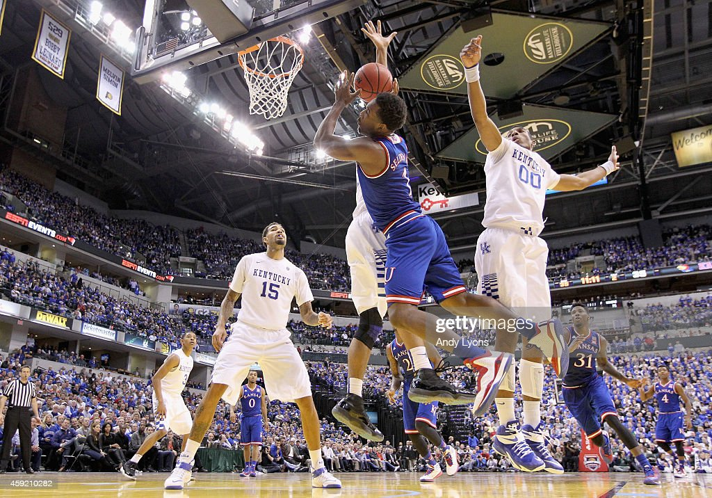 Wayne Seldon #1 of the Kansas Jayhawks loses control of the ball while defended by Trey Lyles #41 and Marcus Lee #00 of the Kentucky Wildcats in the State Farm Champions Classic at Bankers Life Fieldhouse on November 18, 2014 in Indianapolis, Indiana.