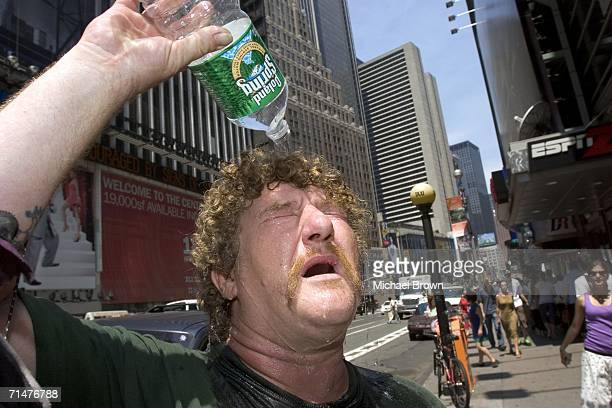 Wayne Semancik of Trenton New Jersey pours water on his head to cool himself off July 18 2006 in New York City Temperatures are expected to stay...