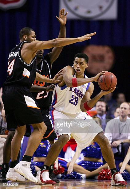 Wayne Simien of the Kansas Jayhawks is double teamed by Joey Graham and Ivan McFarlin of the Oklahoma State Cowboys in the Semifinals of the Phillips...