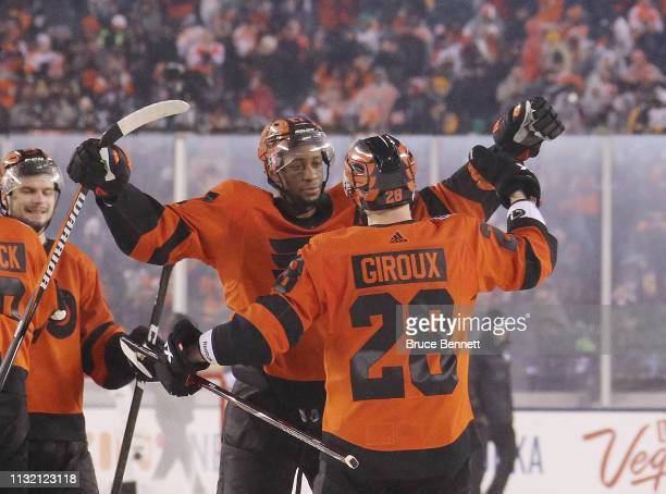 Wayne Simmonds and Claude Giroux of the Philadelphia Flyers celebrate victory against the Pittsburgh Penguins during the 2019 Coors Light NHL Stadium...