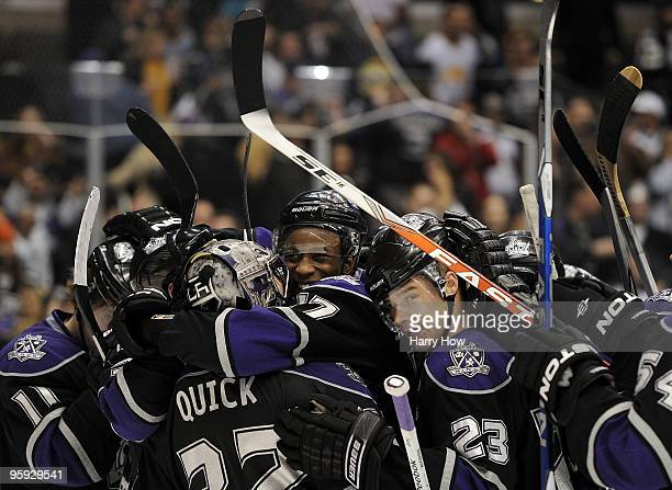 Wayne Simmonds and Dustin Brown of the Los Angeles Kings hug Jonathan Quick after his game winning save on Tim Connolly of the Buffalo Sabres to...