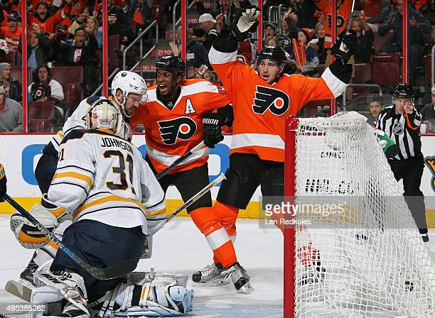 Wayne Simmonds and Matt Read of the Philadelphia Flyers react to react to Brayden Schenn's third period game tying goal against Chad Johnson and...
