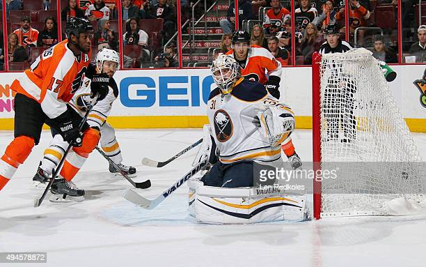 Wayne Simmonds and Matt Read of the Philadelphia Flyers watch as goaltender Chad Johnson of the Buffalo Sabres surrenders a third period goal by...