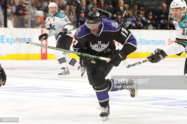 Wayne Simmonds of the Los Angeles Kings skates while being stick checked by Patrick Marleau of the San Jose Sharks on October 12 2008 at Staples...