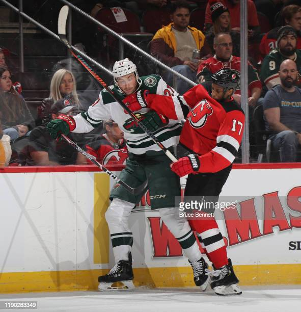 Wayne Simmonds of the New Jersey Devils checks Carson Soucy of the Minnesota Wild into the boards during the first period at the Prudential Center on...