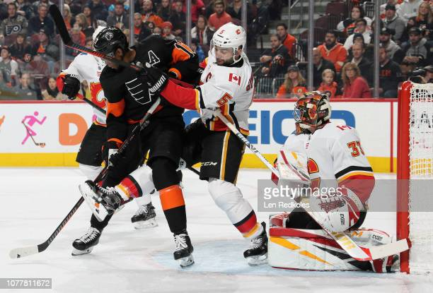 Wayne Simmonds of the Philadelphia Flyers battles for position in front of goaltender David Rittich of the Calgary Flames with Mark Giordano on...