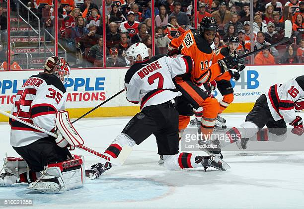 Wayne Simmonds of the Philadelphia Flyers battles with John Moore of the New Jersey Devils in front of goaltender Cory Schneider on February 13 2016...