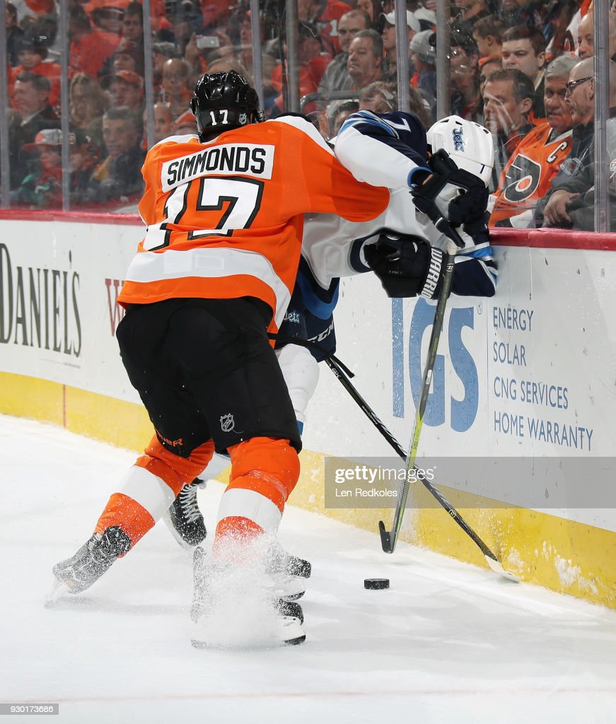 Wayne Simmonds #17 of the Philadelphia Flyers checks Ben Chiarot #7 of the Winnipeg Jets into the boards as they battle for the loose puck on March 10, 2018 at the Wells Fargo Center in Philadelphia, Pennsylvania. The Flyers went on to defeat the Jets 2-1.