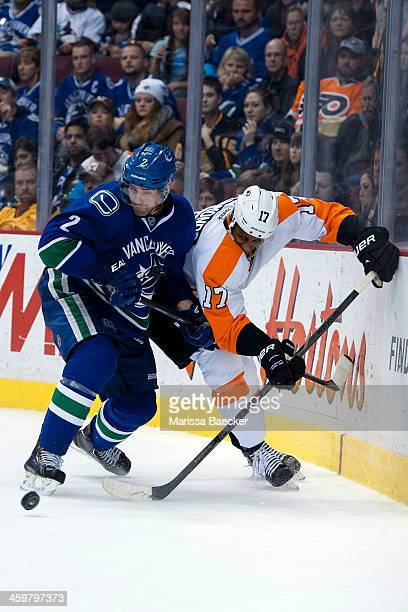Wayne Simmonds of the Philadelphia Flyers digs for the puck as Dan Hamhuis of the Vancouver Canucks checks him into the boards on December 30 2013 at...