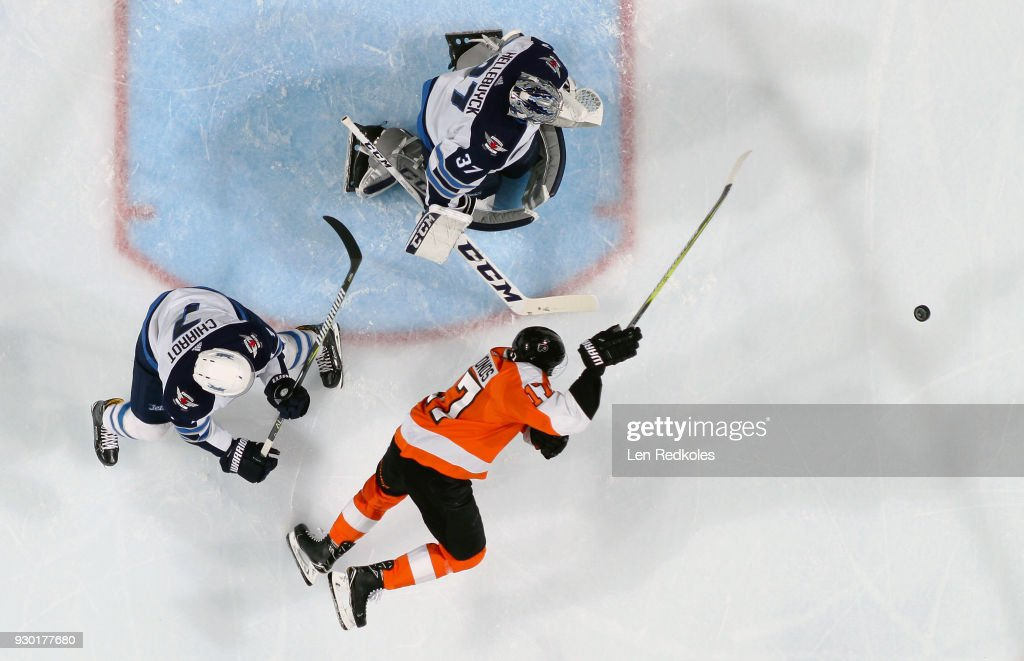 Wayne Simmonds #17 of the Philadelphia Flyers is tripped by Ben Chiarot #7 of the Winnipeg Jets while playing the loose puck in front of Connor Hellebuyck #37 on March 10, 2018 at the Wells Fargo Center in Philadelphia, Pennsylvania. The Flyers went on to defeat the Jets 2-1.