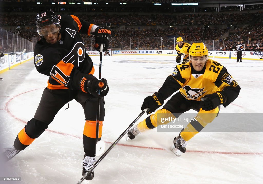 Wayne Simmonds #17 of the Philadelphia Flyers plays the puck around the boards as Cameron Gaunce #24 of the Pittsburgh Penguins pursues the play in the first period of the 2017 Coors Light NHL Stadium Series at Heinz Field on February 25, 2017 in Pittsburgh, Pennsylvania.
