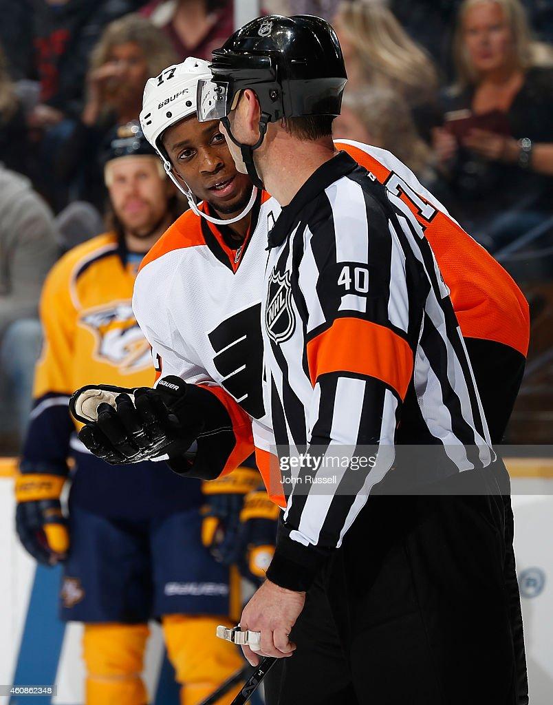 Wayne Simmonds #17 of the Philadelphia Flyers questions referee Steve Kozari #40 on a penalty call against the Nashville Predators at Bridgestone Arena on December 27, 2014 in Nashville, Tennessee.