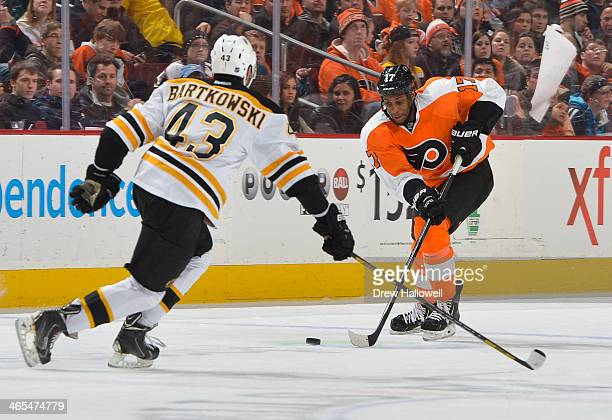 Wayne Simmonds of the Philadelphia Flyers skates at Matt Bartkowski of the Boston Bruins at the Wells Fargo Center on January 25 2014 in Philadelphia...