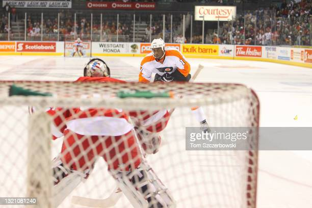 Wayne Simmonds of the Philadelphia Flyers skates in on goal during the shootout as a fan throws a banana onto the ice against the Detroit Red Wings...