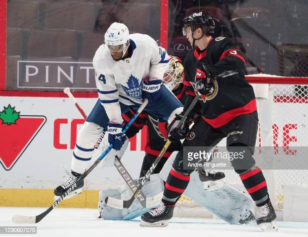 Wayne Simmonds of the Toronto Maple Leafs jumps as he screens Matt Murray of the Ottawa Senators with Josh Brown defending at Canadian Tire Centre on...