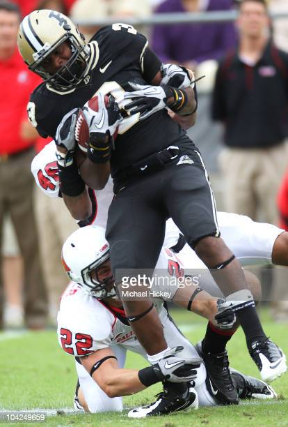 Waynelle Gravesande of the Purdue Boilermakers is tackled by Derrick Henry and Ray Winkler of the Ball State Cardinals at RossAde Stadium on...