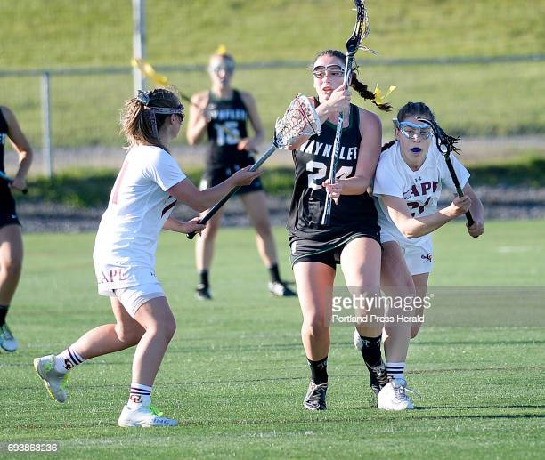 Waynflete's Ali Pope drives with the ball as Cape Elizabeth's Chloe Chapin left and Casey Kelley try and slow her down Wednesday June 7 2017