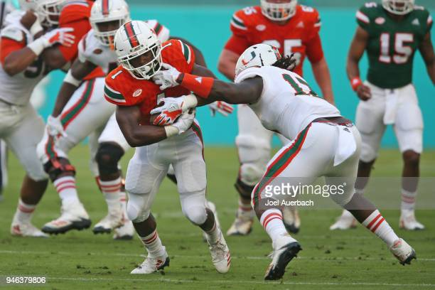 Waynmon Steed defends against Lorenzo Lingard of the Miami Hurricanes as he runs with the ball during the spring game on April 14 2017 at Hard Rock...