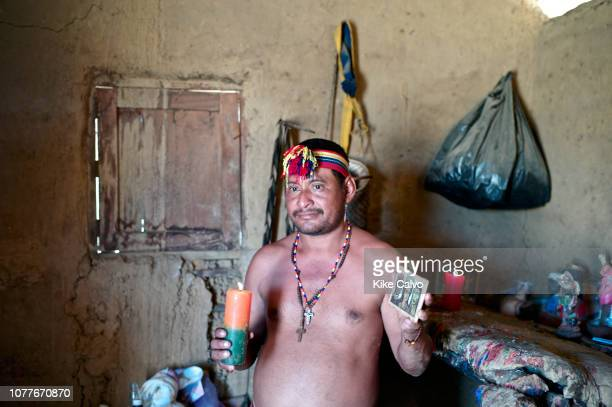 A Wayuu Piachi or Healer follower of Maria Lionza religion holds postcards of Guaicaipuro Maria Lionza Negro Felipe and Dr Jose Gregorio Hernandez...