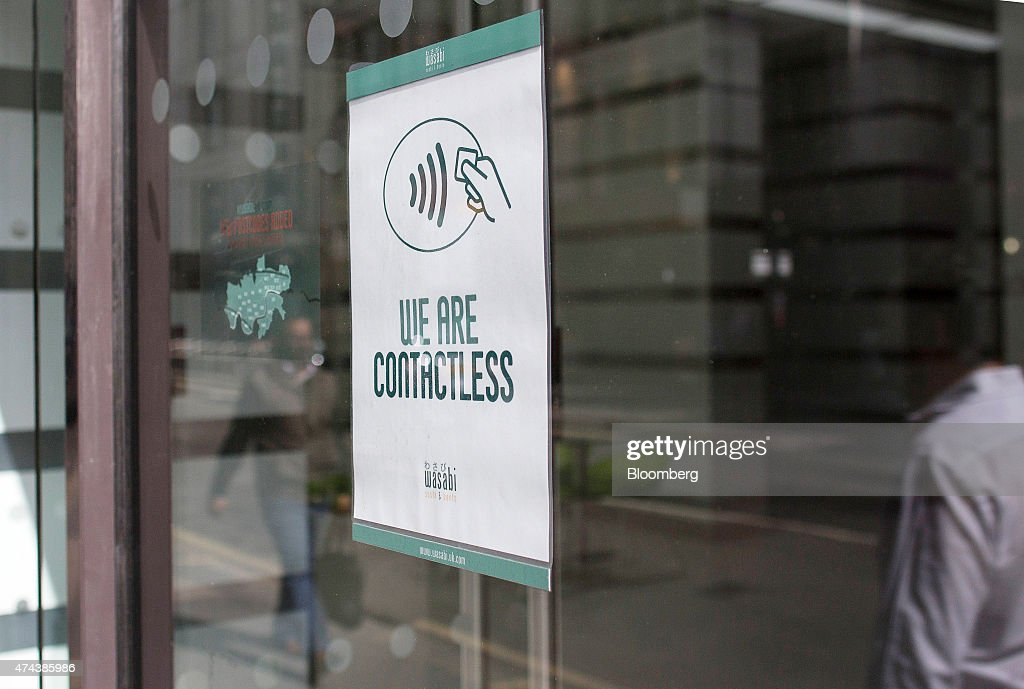A 'We Are Contactless' sign advertising the acceptance of contactless payment sits in the window of a Wasabi sushi restaurant in London, U.K., on Friday, May 22, 2015. Credit and debit cards that can be used by tapping the reader are gaining users, and mobile apps are set to further boost the popularity of contactless paying. Photographer: Simon Dawson/Bloomberg via Getty Images