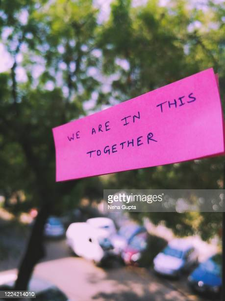 we are in this together. covid-19 crisis. - text schriftsymbol stock-fotos und bilder