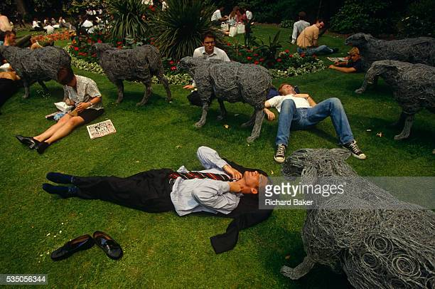 We are looking down from above to office and business workers who are lying down and relaxing in the grass in their lunch break at Finsbury Circus a...