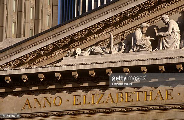 We are looking up from below at a Latin inscription describing the era of Elizabethan rule a classic neoRomanesque architecture of the Royal Exchange...