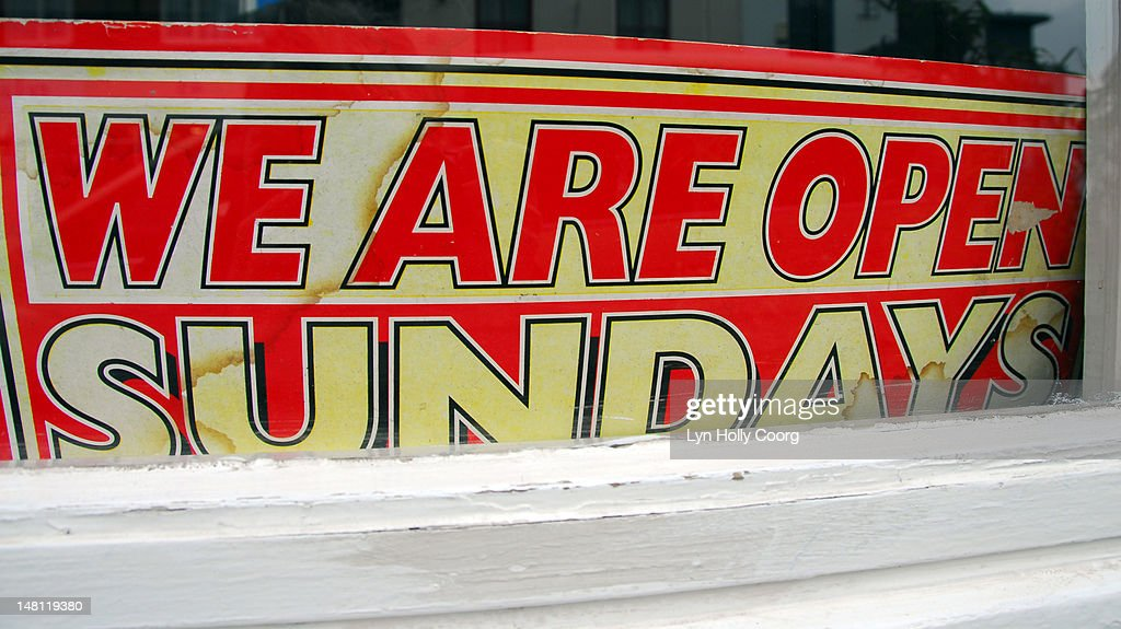 'We are open sundays', old sign in a window : Stock Photo