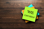 We Can Help, the phrase is written on multi-colored stickers, on a brown wooden background. Business concept, strategy, plan, planning.
