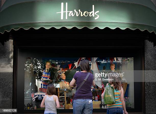 We can see the backs of two girls and their mother admiring a window display depicting three princes, Charles and his two sons William and Harry at...