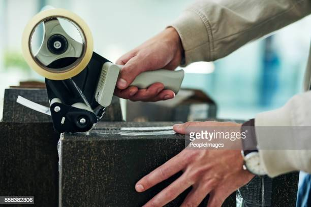 we ensure our packages are all safely secured - tape dispenser stock photos and pictures
