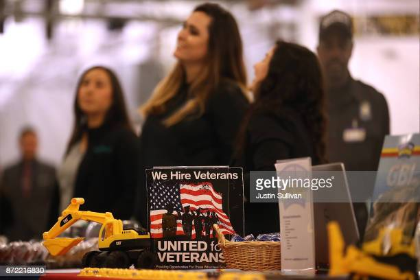 A we hire veterans sign is displayed during a job fair for veterans at the USS Hornet Sea Air Space Museum on November 9 2017 in Alameda California...
