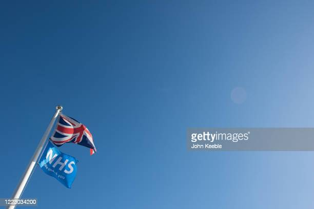"""We Thank You NHS"""" flag and a Union Jack fly together against a clear blue sky on May 05, 2020 in Benfleet, England. The country continued quarantine..."""