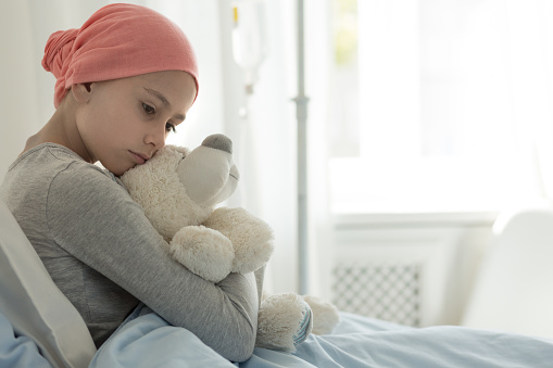 Weak girl with cancer wearing pink headscarf and hugging teddy bear 1048207966