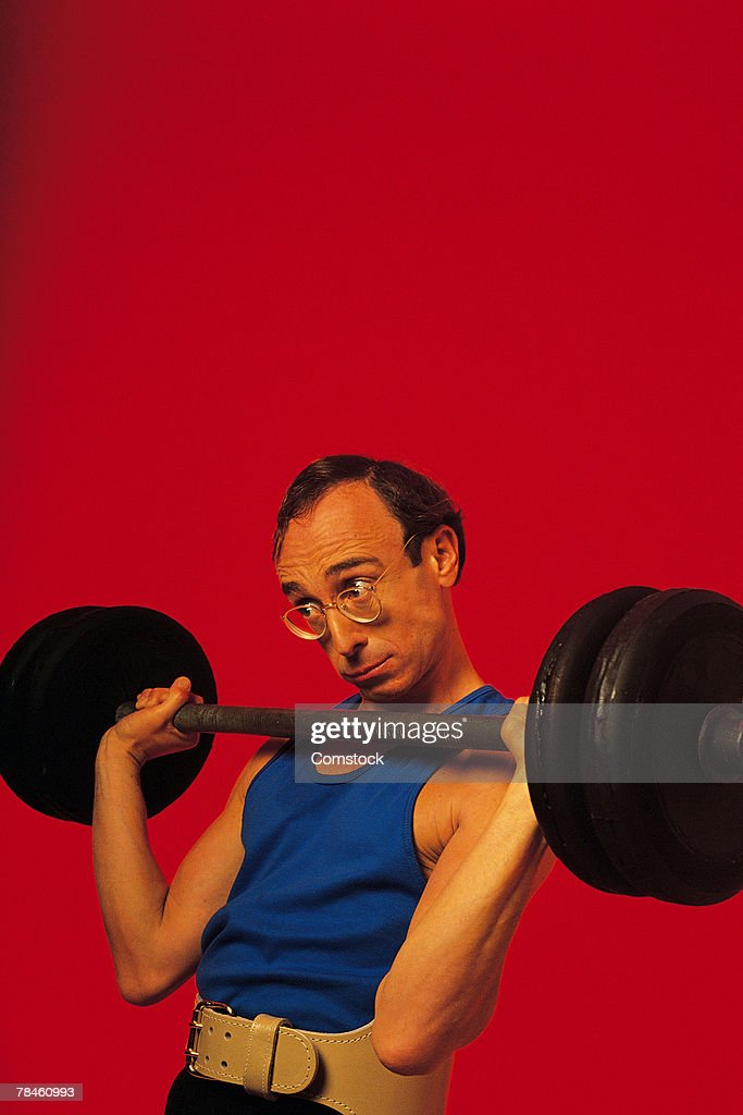 Weak man lifting barbell : Stock Photo
