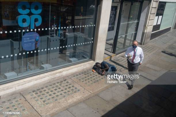 Wealthier man carrying his lunch, walks past a male lying on the pavement outside a branch of the Co-Op bank on the Strand, on 23rd June 2021, in...