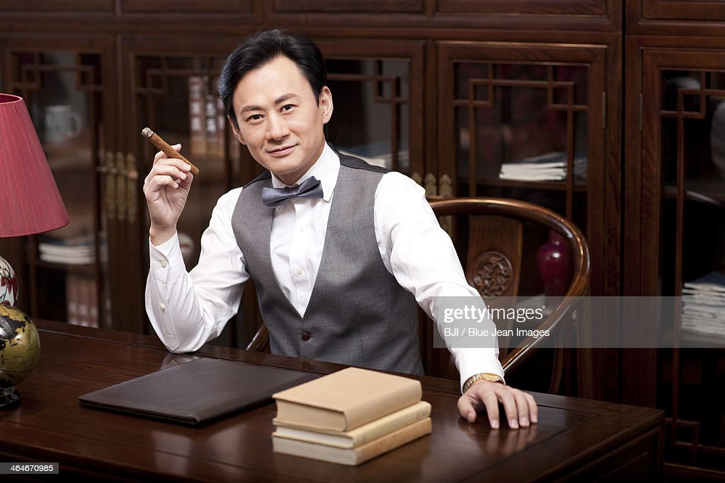 Wealthy Businessman Smoking Cigar Stock Photo
