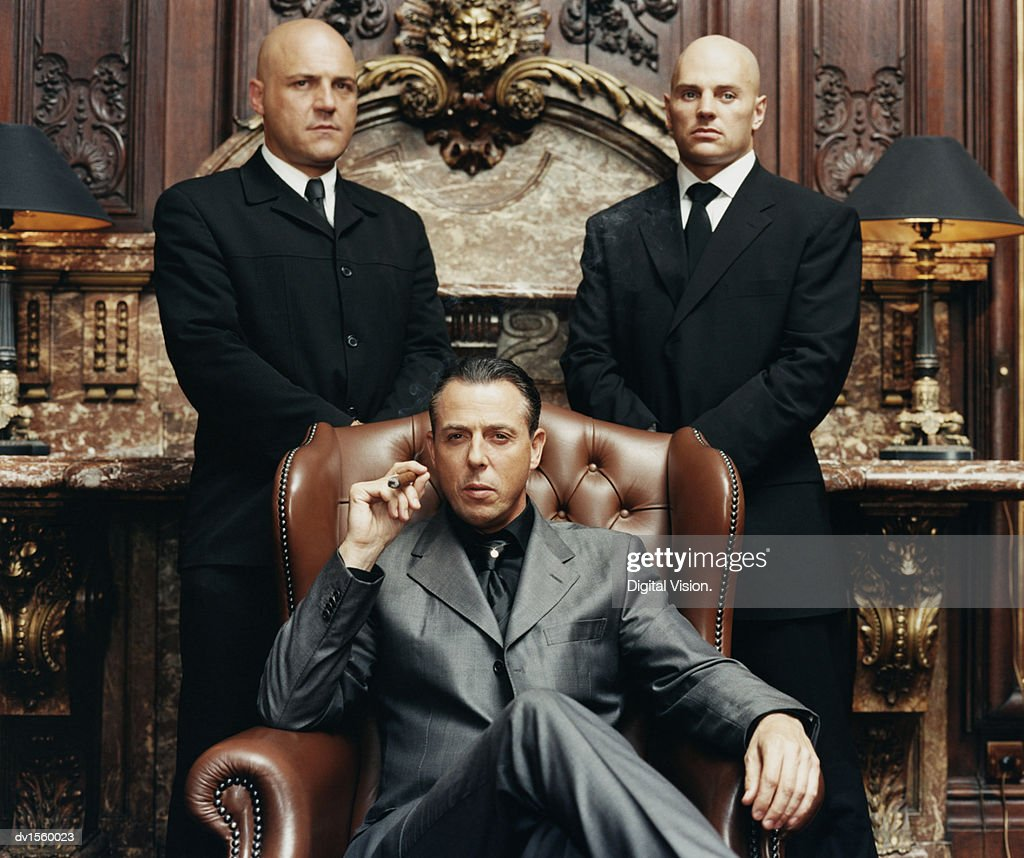 Wealthy Criminal Sitting in an Armchair Between two Bodyguards : Stock Photo