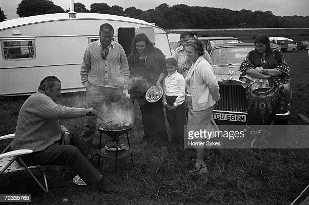 A wealthy gypsy family gather around the barbeque waiting to be served during Derby Day on Epsom Downs 1970 One family member leans against the...