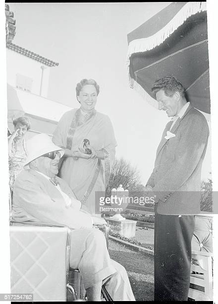Wealthy Indian potentate, the Aga Khan and his wife, the French born Begum, laugh heartily as they enjoy a joke told them by a famed American...