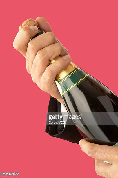 Wealthy Man Uncorking Champagne Bottle