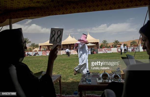 A wealthy Saudi woman bids on an Arabian horse at an auction outside of Riyadh Saudi Arabia March 1 2013 Despite an extremely affluent sector in...