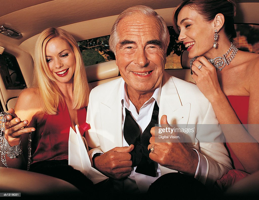 Wealthy Senior Man Sitting Between Young Women in the Back of a Limousine : Stock Photo