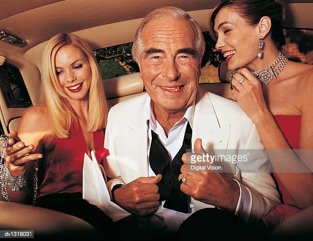 wealthy senior man sitting between young women in the back of a limousine - millionnaire stock photos and pictures