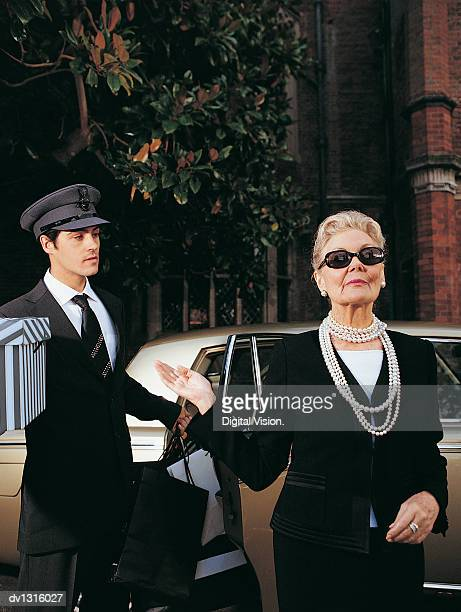 wealthy senior woman in front of her car and chauffeur - smug stock photos and pictures